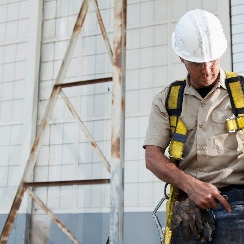worker-putting-on-safety-harness-picture-id171267937